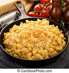 Mac and cheese in a cast iron pan baked with breadcrumbs with steamed broccoli
