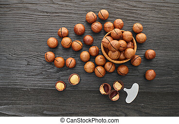 Macadam nut close-up on a black wooden background