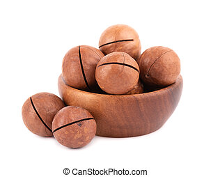 Macadamia nuts in wooden bowl, isolated on white background. Unshelled macadamia