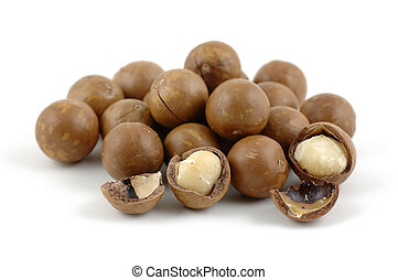 Shelled and unshelled macadamia nuts in isolated white background