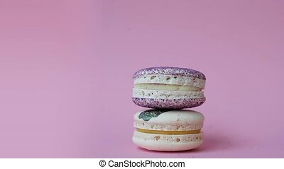 Macaron. Desserts on a bright pink background. Female hand...