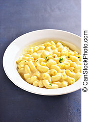 Close up of macaroni and cheese in white bowl on blue stone background.