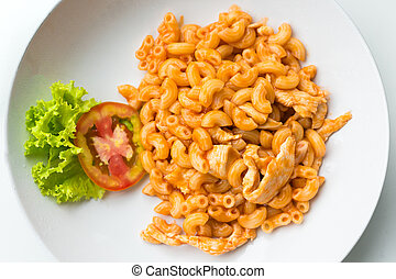 Macaroni and tomato sauce with chicken meat decorated with scallion on a table.