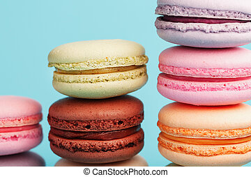 Macaroni cookies of different colors are arranged in the shape of pyramid steps on a blue background.