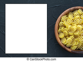Macaroni ruote pasta in a wooden bowl on a black textured background from the side. Close-up with the top. White space for text and ideas.