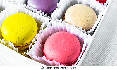 Macarons isolated on a white wooden background...