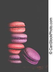 Macarons with a white cup of coffee on a black background.