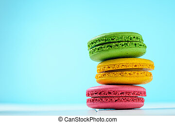 Macaroon cake red and yellow and green on a white table on a light blue background.