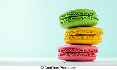 Macaroon cake red and yellow and green on a white wooden table on a blue background.