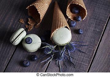 Macaroones in cones around thistles and blueberries