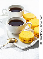 Macaroons and coffee cup on white wood table.