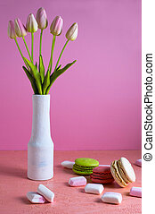 Macaroons and small white and pink marshmallows are scattered on a pale pink background next to a vase of tulips. Place for text.