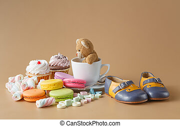 macaroons, marshmallows, cakepops, bear toy and other sweets on beige background at kids birthday party