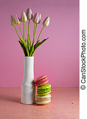 Macaroons on a pale pink background next to a vase of tulips. Place for text.