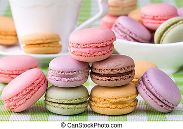 Macaroons with cup of coffee on background