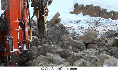 Machine boring terrestrial rocks in winter, pile of ground...