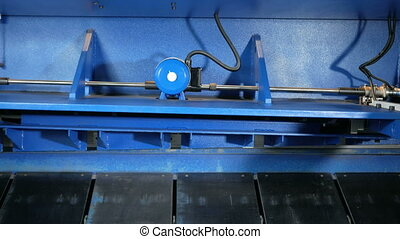 Machine for cutting sheet metal. Large hydraulic guillotine shears. Rear view: a lot of moving parts