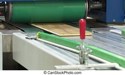 Machine for gluing laminated floor panels. Gluing laminate...
