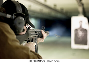 Machine gun - Man shooting machine gun at a target at...
