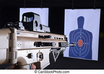 machine gun pointed at bullseye target on gun range -...