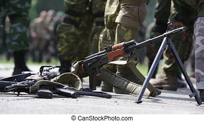 Machine gun - Soldiers crowding around a machine gun, focus...