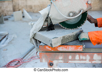 Machine has sharp blade which makes clean cut in stone or granite. It uses abrasive action to slice through material as the saw rotates at high speed. And man builder hands
