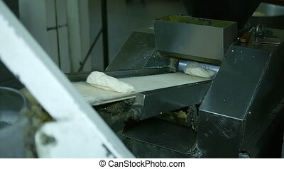 machine rolls the dough for baking