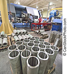 Machine shop - big lathe cutting tubes being operated by ...