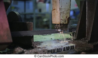 Machine with metal band saw. slow sawing thick piece of pure...