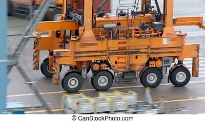 Machine with several wheels rides by asphalt at industrial...