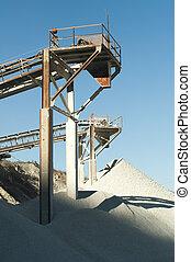 Machinery in a limestone quarry.Piles of limestone rocks
