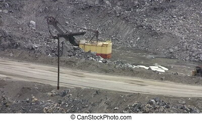 Machines excavate soil in an open pit