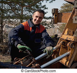 Machinist excavator with a wrench in his hand