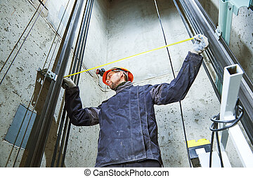 machinist with measure tape checking lift construction in elevator shaft