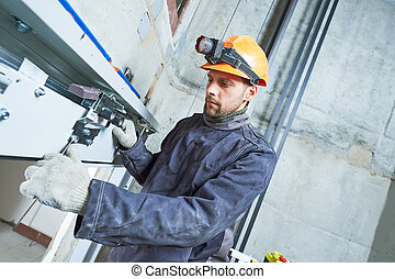 machinist with spanner adjusting lift mechanism in elevator shaft
