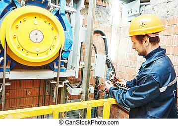 machinist worker adjusting elevator mechanism of lift