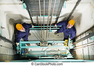 machinists adjusting lift in elevator hoist way - two ...