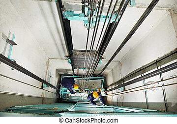 machinists adjusting lift in elevator hoistway - two...