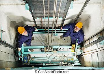 machinists adjusting lift in elevator hoist way - two...