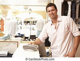 macho, ayudante ventas, en, compruebe, de, tienda de ropa