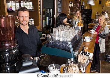 macho, barman, con, colega, trabajando, en, plano de fondo