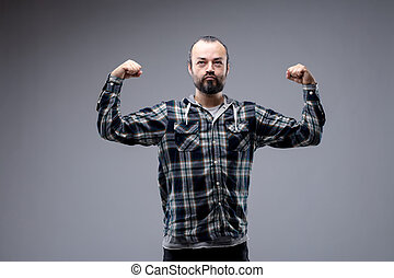 Macho bearded man in casual long sleeved shirt standing flexing his arms with a wry expression in an attempt to show off his biceps isolated on grey with copy space