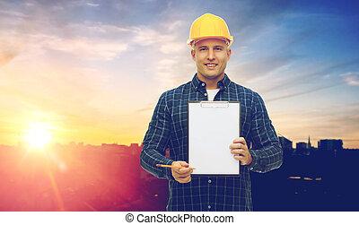 macho, constructor, en, sombrero duro amarillo, con, portapapeles