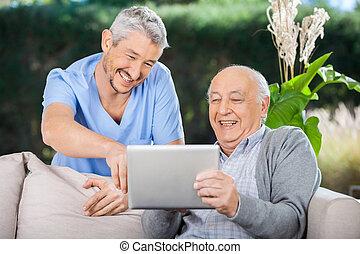 macho, enfermeira, e, homem sênior, rir, enquanto, usando, tablete digital