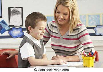 macho, escuela primaria, alumno, y, profesor, trabajo en el escritorio, en, aula