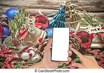 macho, mão, é, segurando, um, modernos, tela toque, telefone, e, ornamento natal