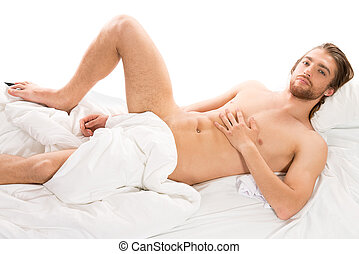macho man - Handsome nude man lying in a bed. Isolated over...