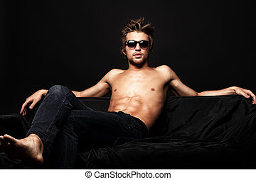 macho man - Sexy shirtless man sitting on a sofa. Black...
