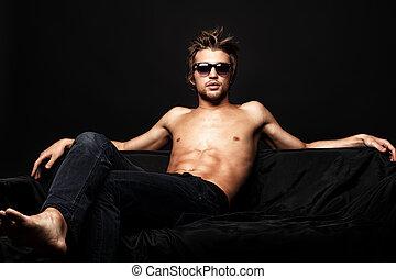 macho man - Sexy shirtless man sitting on a sofa. Black...