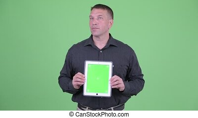 Macho mature businessman thinking while showing digital...